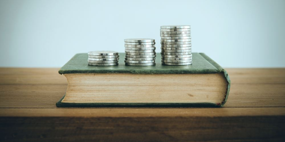 Stack of coins placed upon a book