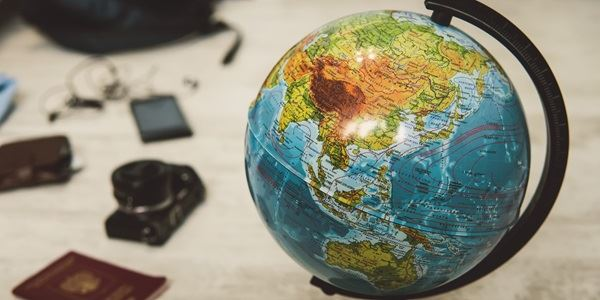 A globe in the front of a passport and a camera