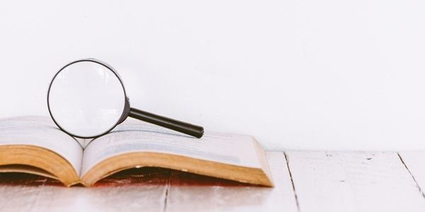 Magnifying glass for investigating on top of a book
