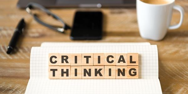 Letters saying critical thinking on a work desk